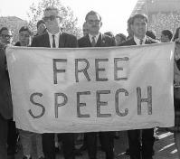 "Men holding up a banner saying ""Free Speech"""